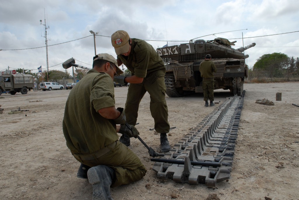 Soldiers repair the track of a tank stationed close to Kibbutz Kissufim, near the the Gaza Strip (photo credit: Almog Sugavker/Flash90)