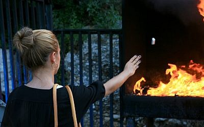 A young woman throws candles into the fire, a popular ritual at the burial site of Rabbi Yonatan ben Uziel (photo credit: Chen Leopold/Flash 90)