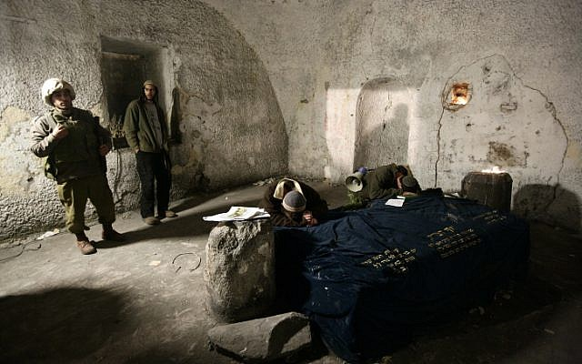 File: Jews at prayer in Joseph's Tomb in the West Bank city of Nablus as IDF soldiers stand guard. (Abir Sultan/Flash90)