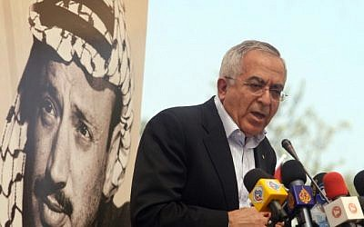 Palestinian Prime Minister Salam Fayyad speaks underneath a poster of a young Yasser Arafat (photo credit: Issam Rimawi/Flash90)