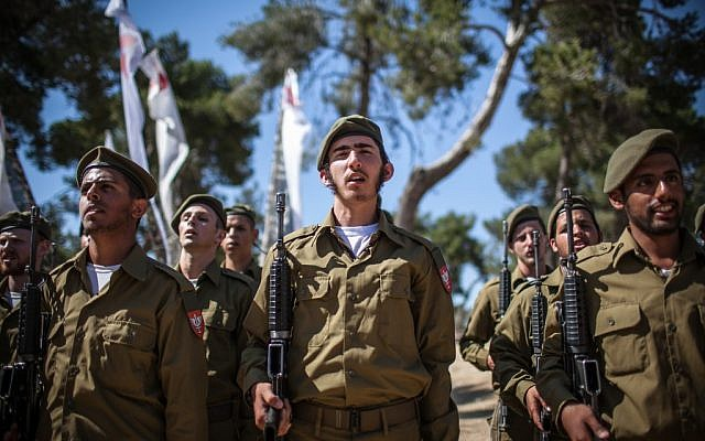 Israel's universal draft is one factor behind the low peacefulness rating. Here, soldiers are being sworn in to a religious IDF unit. (photo credit: Photo by Noam Moskowitz/Flash90)