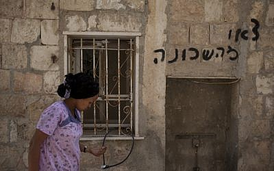 A woman walks past the Jerusalem apartment that had been set on fire on Monday. Spray-painted message reads 'get out of the neighborhood' (photo credit: Yonatan Sindel/Flash90)