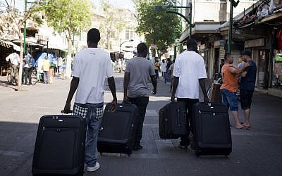 Migrants from South Sudan leave their homes in Tel Aviv last year after the government arranged for them to be sent back to their home country(photo credit: Tali Mayer/Flash90)