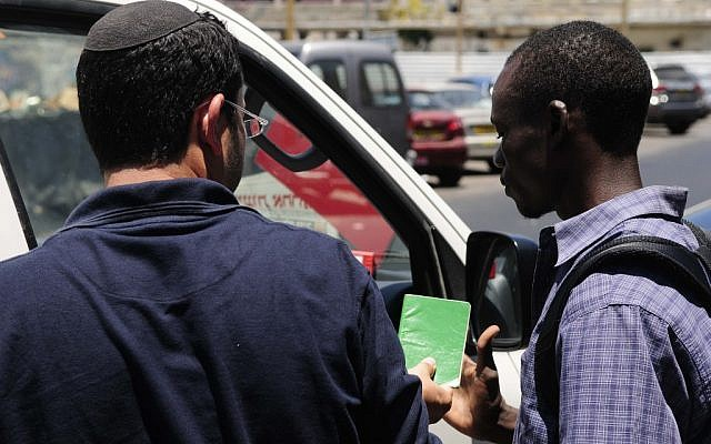 Immigration police check the papers of an African migrant in South Tel Aviv (photo credit: Tomer Neuberg/Flash90)