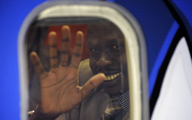 A South Sudanese man waves from inside an airplane at Ben Gurion airport (photo credit: Kobi Gideon/GPO/Flash90)
