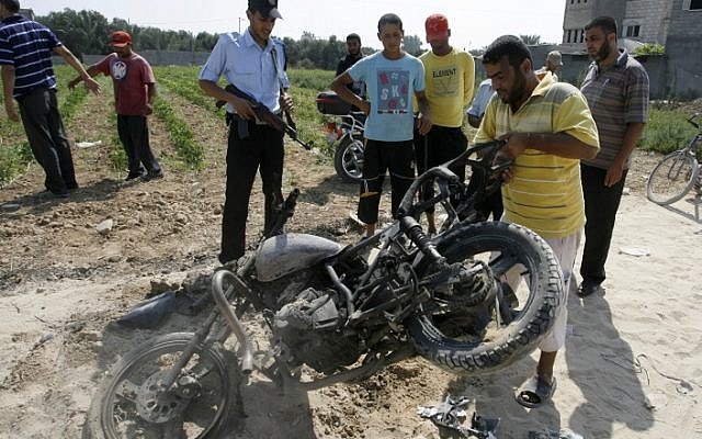 Palestinians inspect a motorcycle that was hit in an Israeli air strike in the Gaza Strip. Two terrorists, both suspected of involvement in the June 18 attack, were targeted. One was killed, the other severely injured. (Photo credit: Abed Ragim Khatib/ Flash 90)
