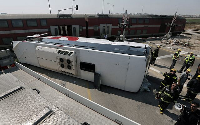 Firemen and emergency workers stand next to a damaged bus at the site of an accident between a bus and a train near Nitzan, Friday (photo credit: Tsafrir Abayov/Flash90)Firemen and emergency workers stand next to a damaged bus at the site of an accident between a bus and a train near Nitzan, Friday (photo credit: Tsafrir Abayov/Flash90)