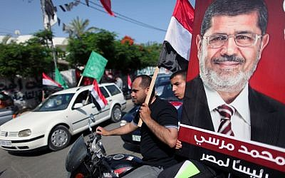 Palestinian Hamas supporters in the streets of Gaza City hold up Egyptian flags and the poster of Mohammed Morsi as they celebrate his victory in the Egyptian elections, in June (photo credit: WIssam Nassar/Flash90)