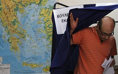 A Greek man leaving a polling booth in Athens on Sunday. (photo credit: AP/Petros Karadjias)