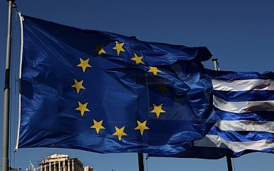An EU and Greek flag fly in front of the ancient Parthenon temple in Athens on Sunday (photo credit: Petros Giannakouris/AP)