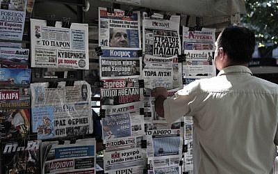 A Greek man looks at the front pages of newspapers on Saturday, the day before general elections. (photo credit: Dimitri Messinis/AP)
