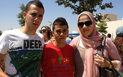 Zahir (center) and his brother and mother, Kifach, at the Jordan River Village grand opening Sunday. The camp has made Zihar very happy, said Kifach. (photo credit: Michal Shmulovich)