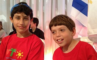 Eyal Adler (left) and his friend Benjamin sit patiently during the grand opening ceremony of the Jordan River Village camp. Eyal suffers from colitis. (photo credit: Michal Shmulovich)