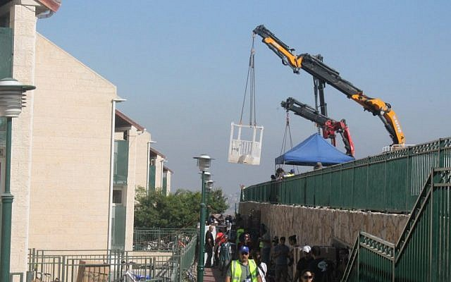 Crews moving belongings out of the Ulpana homes Tuesday. (photo credit: Courtesy Israel Vandy/Bureau of Yaakov Katz)