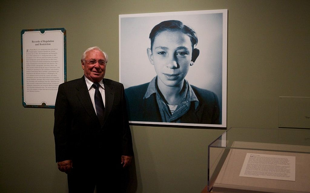 "Holocaust survivor Michael Pupa standing next to his childhood photo in the ""Attachments"" exhibit at the National Archives in Washington, DC. (photo credit: Earl McDonald for the National Archives/JTA)"