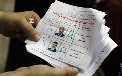 A man holds a ballot reading 'Down with the military regime' (photo credit: AP/Amr Nabil)