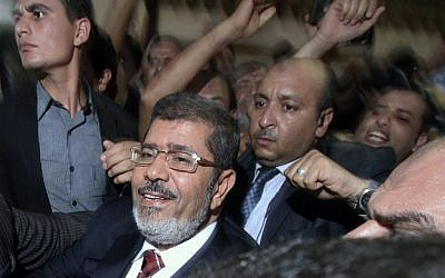 Muhammad Morsi celebrates his apparent victory in Cairo last Monday (photo credit: AP/Ahmed Gomaa)