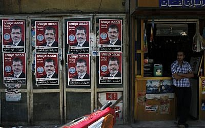 A worker stands in front of his shop next to posters with pictures of presidential candidate Mohammed Morsi in Cairo, Egypt, Wednesday (photo credit: Nasser Nasser/AP)