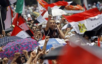 An Egyptian supporter of the Muslim Brotherhood's candidate for president, Mohammed Morsi, raises his shoe in protest as he shouts slogans in Tahrir Square, Cairo, Egypt, Friday. (photo credit: AP/Amr Nabil)