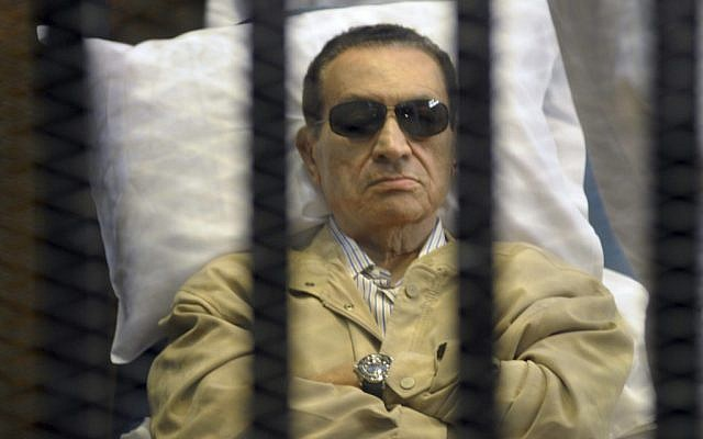 Egypt's ex-President Hosni Mubarak lays on a gurney inside a barred cage in the police academy courthouse in Cairo, Egypt, June 2, 2012 (photo credit: AP)