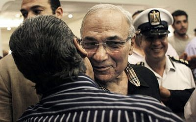 Egyptian presidential runoff candidate Ahmed Shafiq is greeted by a supporter after attending a press conference in Cairo, Egypt (photo credit: AP/Nasser Nasser)