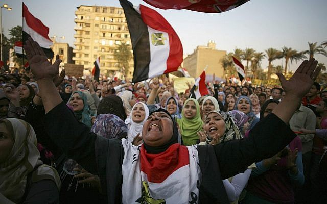 An Egyptian woman draped in the national flag shouts slogans at a protest in Tahrir Square in Cairo last week (photo credit: AP/Manu Brabo)
