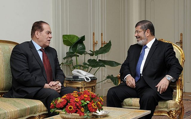 Mohammed Morsi meets caretaker Prime Minister Kamal el-Ganzouri Monday (photo credit: AP Photo/Middle East News Agency)