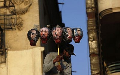 An Egyptian protester carries the image of Mubarak and his aides in a Cairo protest (photo credit: AP Photo/Nasser Nasser)