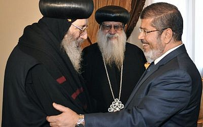 Egyptian President Mohammed Morsi shakes hands with a representative from the Coptic community, in Cairo, June 2012 (photo credit: Middle East News Agency/AP)