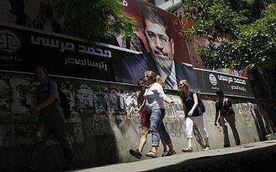 Tourists walk past a campaign poster supporting Egyptian presidential candidate Mohammed Morsi in Cairo (photo credit: AP Photo/Amr Nabil)