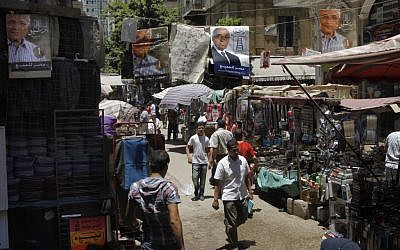 Campaign posters supporting Egyptian presidential candidate Ahmed Shafiq hang above a popular market in Cairo, Egypt (photo credit: Amr Nabil/AP)