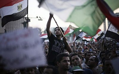 Egyptian protesters wave national flags and banners in Tahrir Square in Cairo on Thursday. (photo credit: Manu Brabo/AP)