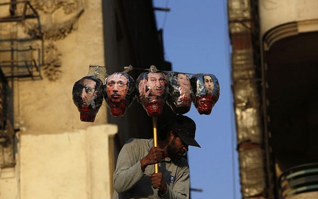 An Egyptian protester carries symbolic heads depicting ousted President Hosni Mubarak, center, and from left, his son Alaa, his interior minister Habib al-Adly, wife Suzanne and son Gamal during a rally protesting the outcome of the Mubarak trial at Tahrir Square, Cairo, Egypt, Tuesday (photo credit: AP/Nasser Nasser)