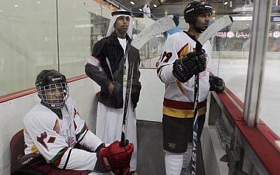 An Emirati organizer and two Omani hockey players watch a match with Kuwait in Abu Dhabi, United Arab Emirates (photo credit: AP/Kamran Jebreili)