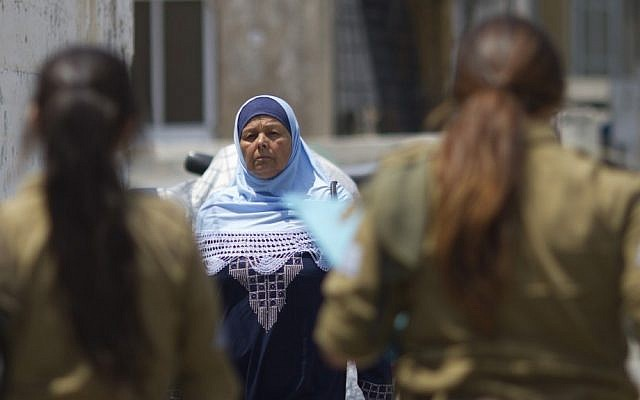 An Arab Israeli woman walks past female IDF soldiers (photo credit: AP/Ariel Schalit/File)