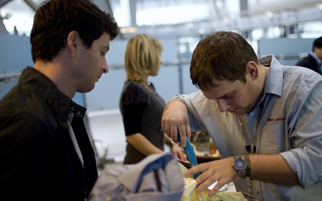 A passenger has his luggage checked by security personnel at Ben Gurion Airport. (photo credit: AP/Ariel Schalit, File)