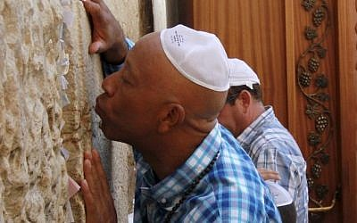 Hip hop mogul Russell Simmons kisses the stones of the Western Wall in Jerusalem's Old City, 2012 (photo credit: Blake Sobczak/AP)