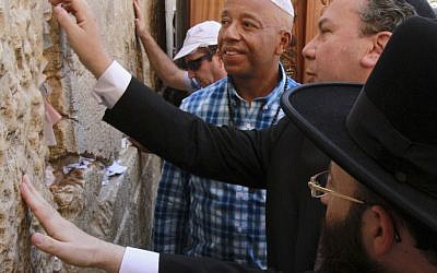 Hip hop mogul Russell Simmons touches stones of the Western Wall in Jerusalem's Old City, Thursday (photo credit: Blake Sobczak/AP)