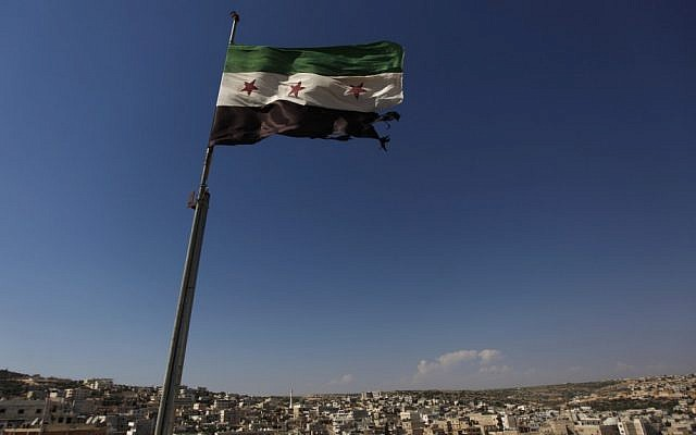 A Syrian revolutionary flag waves on top of a building on the outskirts of Aleppo. (photo credit: Khalil Hamra/AP)