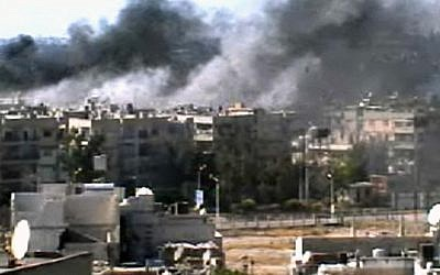 Image capture of explosions in Homs on Monday (photo credit: Bambuser/Homslive via AP video)