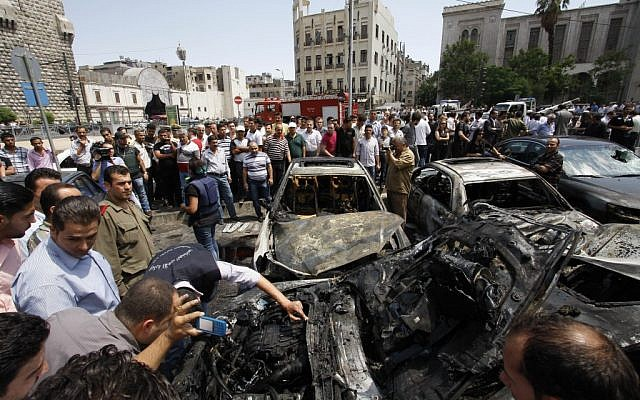 Syrians inspect burned cars at the site of a blast in Damascus. (photo credit: Muzaffar Salman/AP)