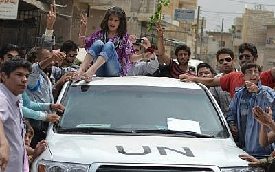 A Syrian girl sits atop a UN observers vehicle during a protest May 29 (photo credit: AP Photo/Edlib News Network ENN)