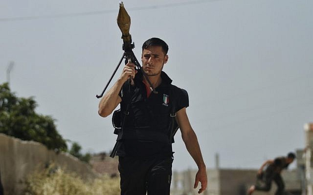 A Free Syrian Army fighter holds a rocket launcher during clashes with Syrian troops near Idlib, Syria, Friday. (photo credit: AP)