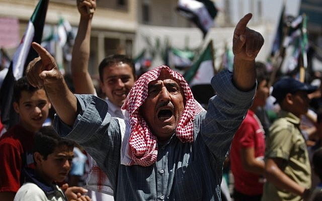 A Syrian man chants slogans during an anti-Bashar Assad protest after Friday prayers on the outskirts of Idlib, Syria. (AP)