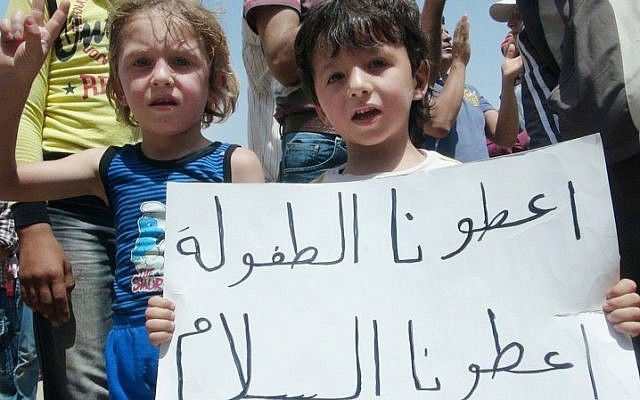 """Syrian children hold a poster that reads, """"Give us a childhood give us peace, and that's all,"""" during a demonstration in Idlib. (photo credit: Local Coordination Committees in Syria/AP)"""
