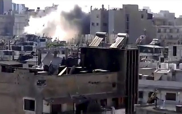 This image made from amateur video released by Shaam News Network shows shelling in Joret el-Shayah, Homs, Syria. (photo credit: AP/Shaam News Network)