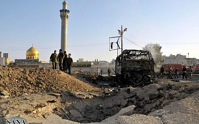 Syrian soldiers stand at the explosion site where a car bomb exploded near the shrine of Sayyida Zeinab, Thursday, June 14, 2012. (photo: AP/SANA)