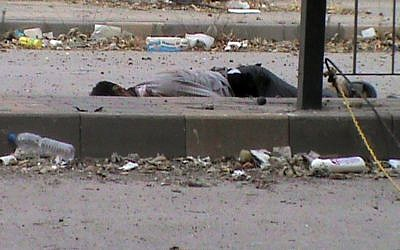A body lying in the streets of Homs, June 21 (photo credit: AP/Shaam News Network, SNN)