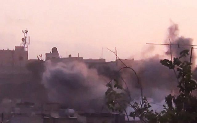 In this image made from amateur video released by the Shaam News Network smoke rises from buildings following purported shelling in Homs on June 26th 2012. (photo credit: AP/Shaam News Network)