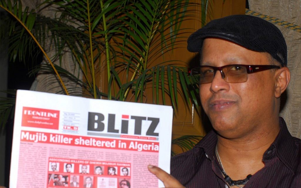 Salah Uddin Shoaib Choudhury holding the English-language Weekly Blitz. (photo credit: Larry Luxner/JTA)